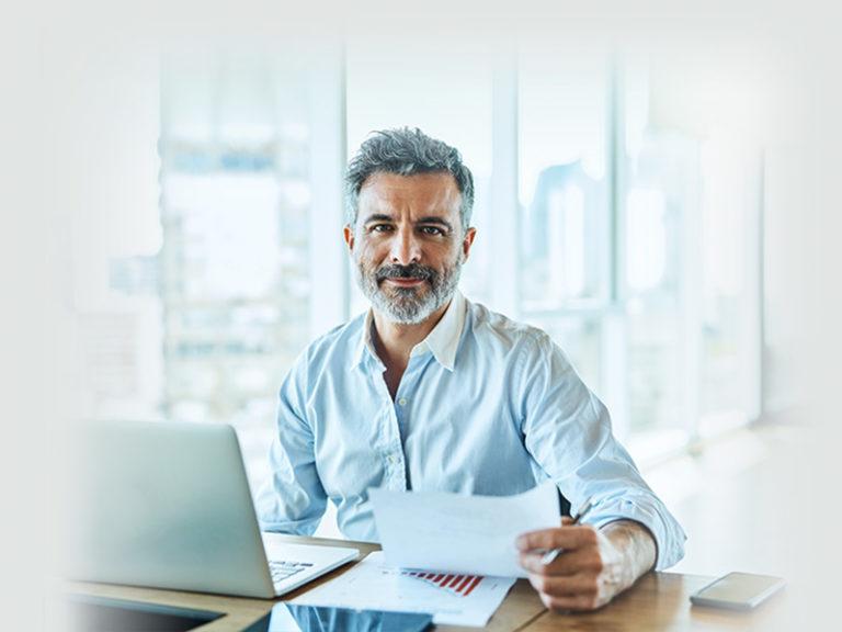 homme cheveux poivre et sel assis devant un bureau ordinateur portable et facture devant lui
